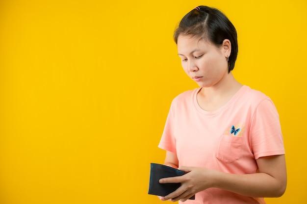 Портрет женщины, держащей бумажник, сожалеющей о том, что в ее кошельке нет денег на желтом фоне. сохранение концепции.