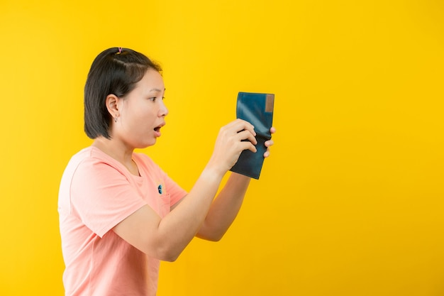 黄色の背景に財布にお金がないことを後悔している財布を持っている女性の肖像画。コンセプトの保存。