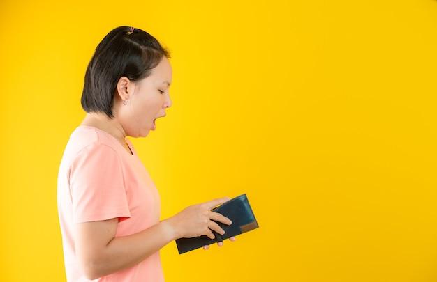 財布を持っている女性の肖像画は、黄色の背景に対して彼女の財布にお金がないことに驚いた。概念の節約。