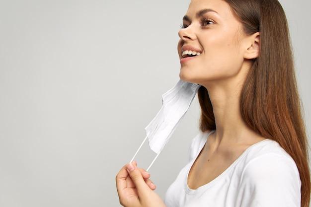 女性の肖像画医療マスクを手に持って側面の保護具を見て微笑む