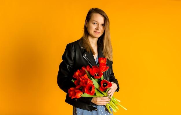 テキスト用のスペースと黄色の背景に赤いチューリップの花束を保持している黒い革のジャケットの女性の肖像画