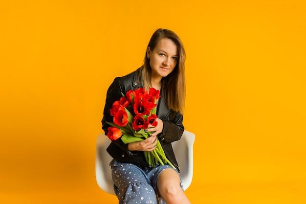 白い椅子に座って、黄色の壁にチューリップの花束を保持している青いドレスと黒い革のジャケットを着た女性の肖像画