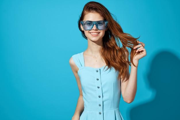 青いドレスの青い背景のライフスタイルの女性の肖像画