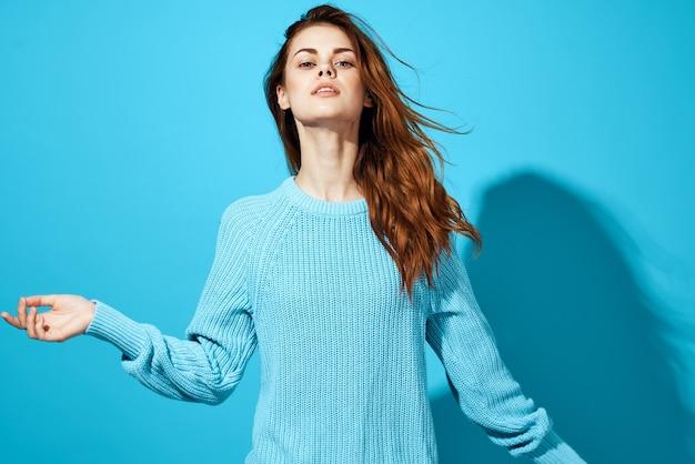 青いセーターの青い背景のライフスタイルの女性の肖像画。高品質の写真