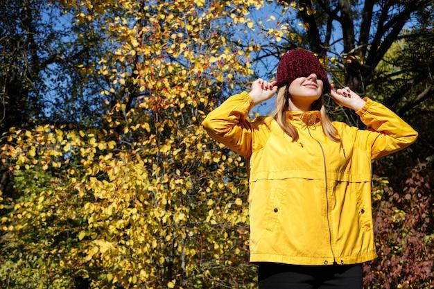 紅葉の前にバーガンディの帽子をかぶった女性の肖像画。秋の気分