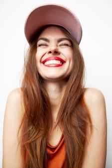 目を閉じて笑顔の帽子をかぶった女性の肖像画楽しいモデル赤いサンドレスのクローズアップ