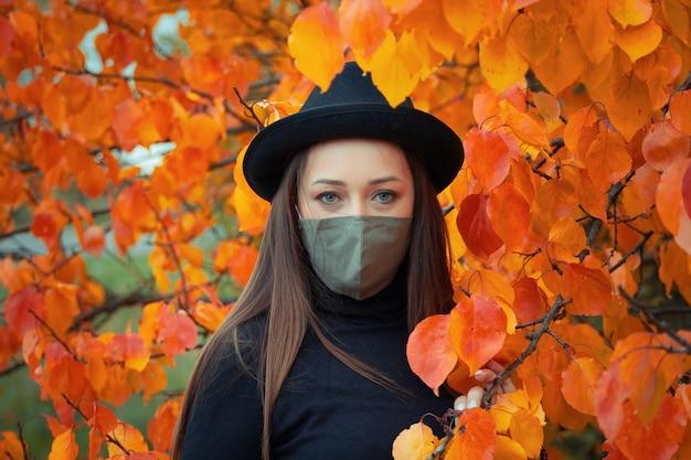 秋の木の上の帽子とマスクの女性の肖像画