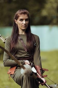 Портрет женщины в средневековом костюме со стрелами и луком на размытом фоне, крупным планом