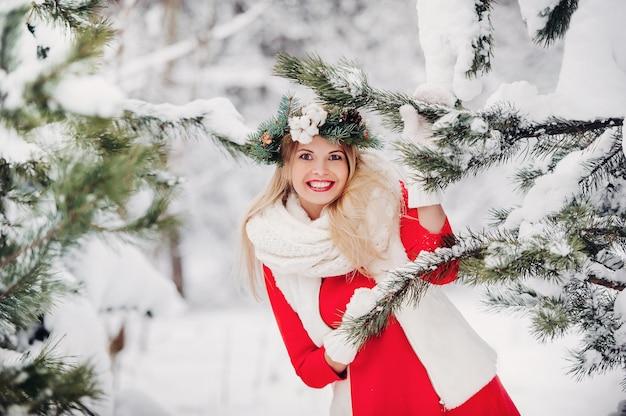 Портрет женщины в красной куртке в холодном зимнем лесу. девушка с венком на голове в заснеженном зимнем лесу