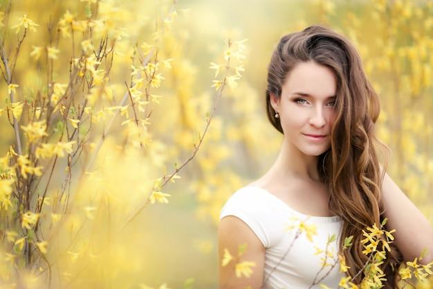 花と黄色の茂みの背景に白いドレスを着た女性の肖像画