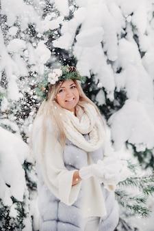 寒い冬の森の白い毛皮のコートを着た女性の肖像画。雪に覆われた冬の森で頭に花輪を捧げる少女。