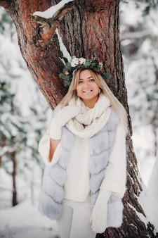 Портрет женщины в белой шубе в холодном зимнем лесу. девушка с венком на голове в заснеженном зимнем лесу