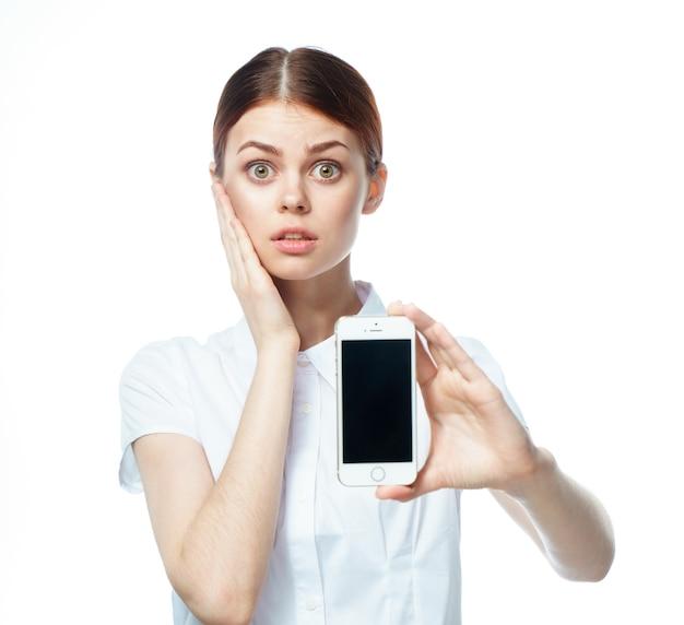 携帯電話を保持している白いシャツの女性の肖像画