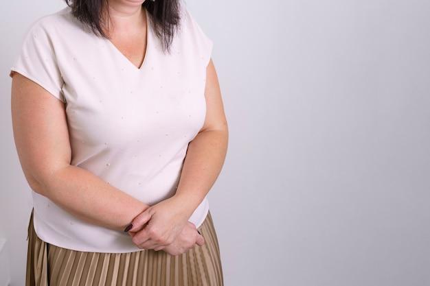 白いtシャツとスカートを着た女性の肖像画で、両手をお腹に折りたたんでワイに撃ちました...