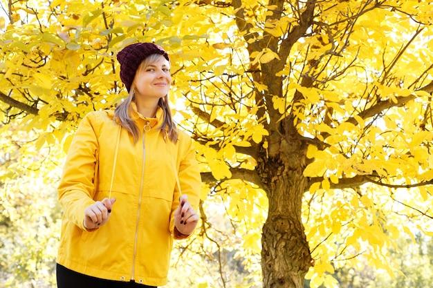 秋の黄色の木の前に黄色いレインコートを着た女性の肖像画。テキスト用の空き容量