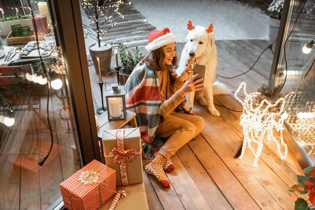 クリスマスの帽子をかぶった女性と、家で年末年始を祝うかわいい犬と格子縞の女性の肖像画、ジンジャーブレッドクッキーを犬に与え、自分撮り写真を作成する