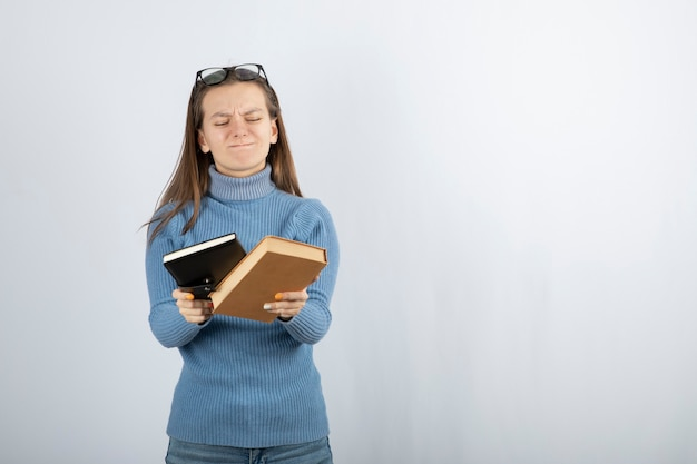 흰색 회색 배경에 두 권의 책을 들고 안경에 여자의 초상화.