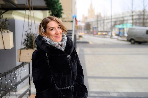 街の通りでファッショナブルな冬の毛皮のコートを着た女性の肖像画