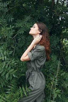 茂みの近くの緑のオーバーオールの女性の肖像画は手で自分自身に触れます緑の葉のクローズアップ