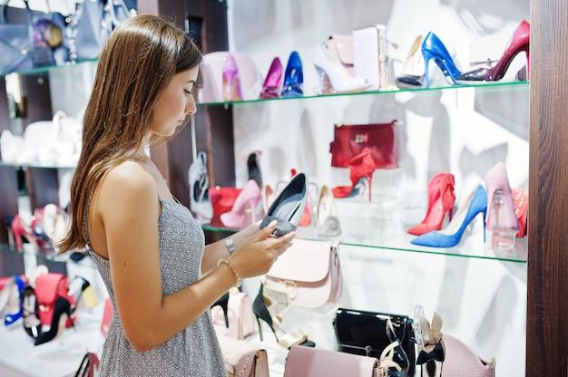 店で女性の靴のペアを選択する灰色のドレスを着た女性の肖像画。