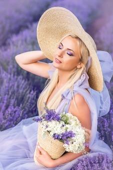 라벤더에있는 여자의 초상화입니다. 아름 다운 여자는 보라색 꽃의 배경에 앉아있다. 보라색 눈 화장.