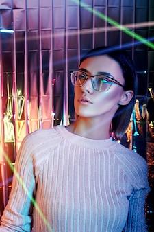 Портрет женщины в неоновых очках отражения на заднем плане. хорошее зрение, идеальный макияж на лице девушки. художественный портрет бликов и боке на очках. восстановление зрения, глазная хирургия