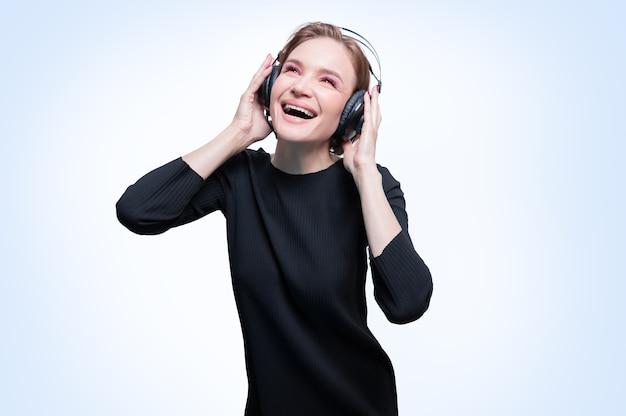 Портрет женщины в профессиональных наушниках. белый фон. dj концепция. смешанная техника