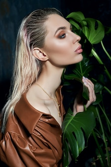 Портрет женщины в тропической зелени. влажные волосы, идеальная фигура и макияж