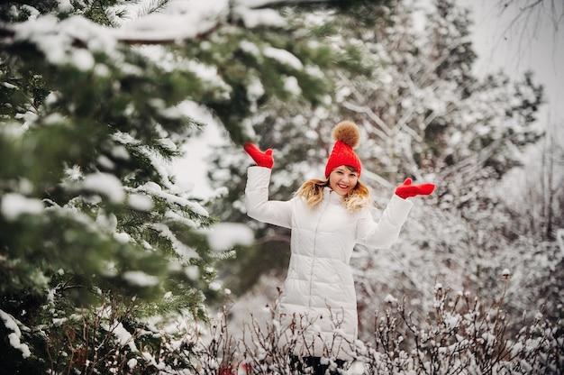 寒い冬の森の白い服と赤い帽子の女性の肖像画。雪に覆われた冬の森の少女