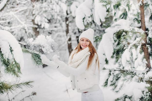Портрет женщины в белой одежде в холодном зимнем лесу. девушка в белой шляпе на голове в заснеженном зимнем лесу