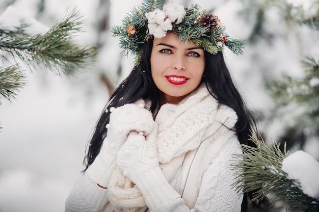 寒い冬の森で白い服を着た女性の肖像画。雪に覆われた冬の森で頭に花輪を捧げる少女。