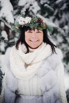 Портрет женщины в белой одежде в холодном зимнем лесу. девушка с венком на голове в заснеженном зимнем лесу
