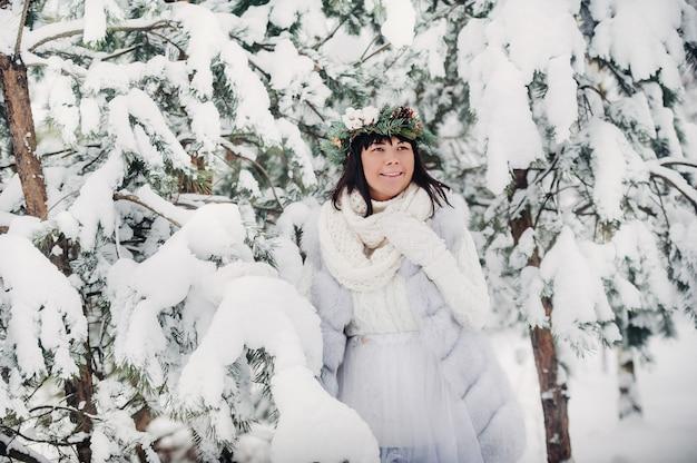 Портрет женщины в белой одежде в холодном зимнем лесу