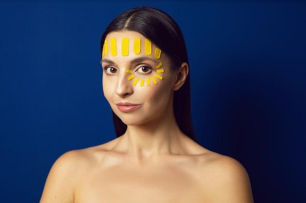 Портрет обнаженной женщины на синей стене с кинезиотейпом лица на лбу