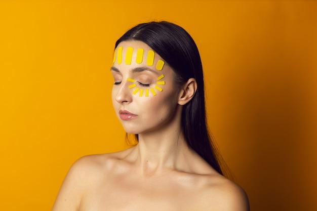 Портрет обнаженной женщины на желтой стене с кинезиотейпом лица на лбу