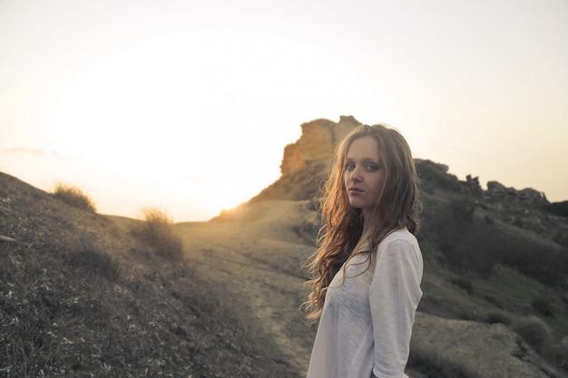 夕暮れ時の山の上の女性の肖像画