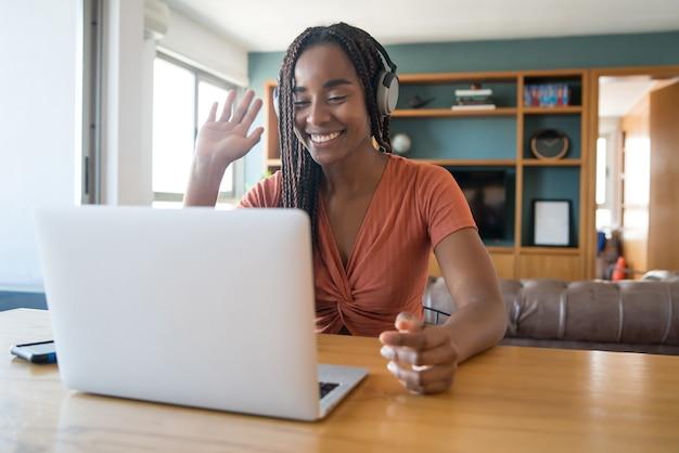 가정에서 일하는 동안 노트북과 헤드폰으로 화상 통화에 여자의 초상화. 홈 오피스 개념.