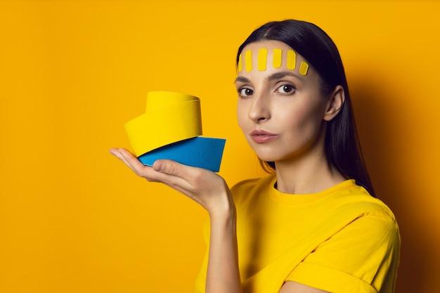 Портрет женщины на желтой стене с кинезиотейпом лица на лбу держит рулон лент