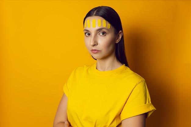 Портрет женщины на желтой стене с кинезиотейпом лица на лбу