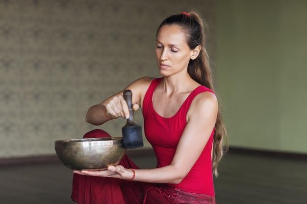 요가를 연습하는 여성의 초상화, 스튜디오에서 금속 그릇을 사용하여 건전한 명상을 수행