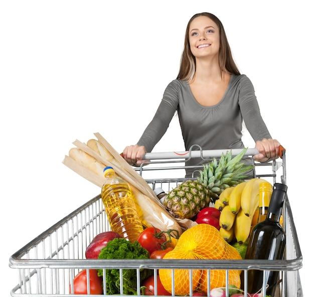 Портрет женщины, толкающей тележку с продуктами
