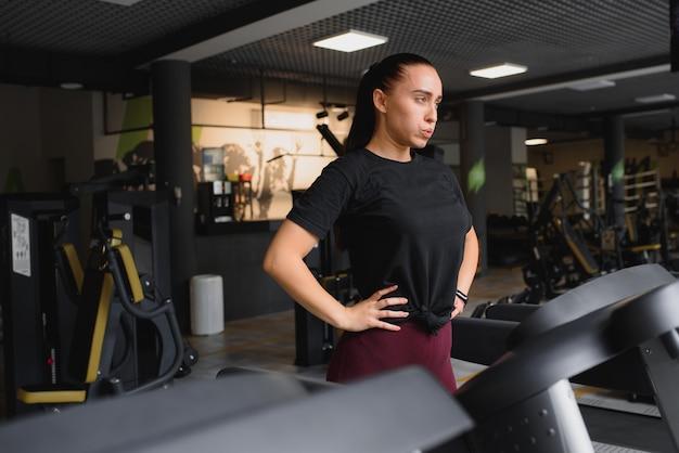彼女のトレーニングの後に休んでいる女性の肖像画。彼女はトレッドミルに寄りかかっており、完全に興奮しているように見えます。