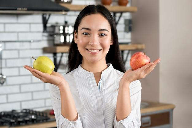 Портрет женщины, показывая здоровое зеленое и красное яблоко в кухне