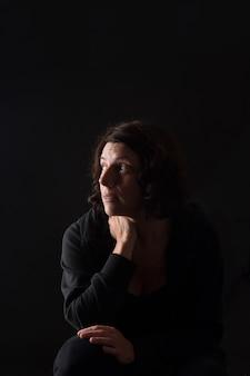 座って黒を見上げる女性の肖像画