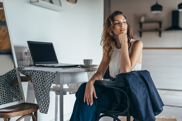 テーブルにノートパソコンを持ってキッチンに座っている女性の肖像画。在宅勤務。