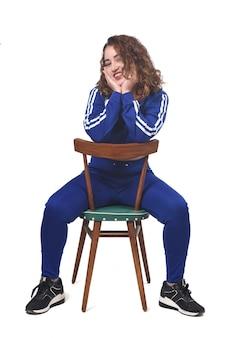 Портрет женщины, сидящей на стуле в белом пространстве, вид сзади стула и смотрящей в камеру
