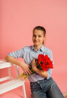 床に座って、スペースのコピーとピンクの壁にチューリップの花束を持っている女性の肖像画