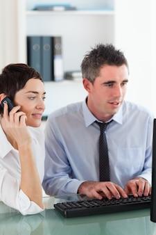 同僚がオフィスでコンピュータを使用しているときに電話をかけている女性の肖像