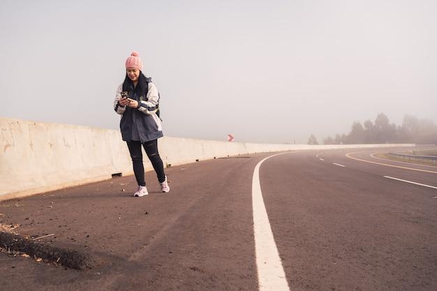스마트폰을 들고 걷고 있는 여성 여행자의 초상화.