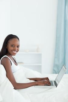 彼女のベッドでラップトップを使用している女性の肖像